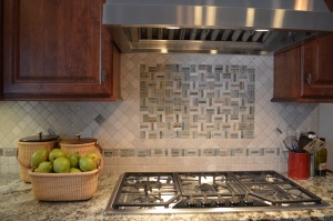 New Tiled Backsplash in a herringbone pattern adds fresh color to the cooking wall in the kitchen.