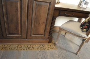 Stenciled flooring for tone on tone textured hardwood floor in the kitchen.